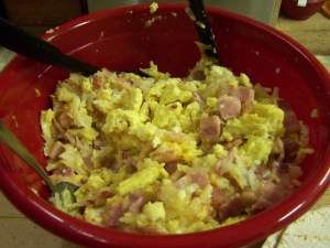 The possibilities of what can go in a breakfast burrito are endless. I scrambled up some eggs with peppers, cooked bacon & drained, then diced, hash browns seasoned with red chili's & onions. After cooking, dump everything together into a large pan or bowl, mix up totally. While mixing I added shredded cheese.