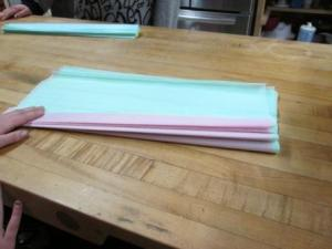 Next you want to fold the paper legnth wise. Remember making the paper fans? Fold forward, then under, forward and under. I had the girls fold an inch or so before creasing the paper.
