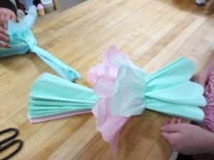 Next, lay your paper on the counter and from one end, lift up 1 sheet to the middle. Remember the paper is thin so try not to rip it.  Lift it up and hold down the other sheets with your free hand.  Gently pull or tug it to the center.
