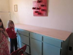 All 3 cabinets together, painted and a plywood top srewed down. I gathered all the girls.